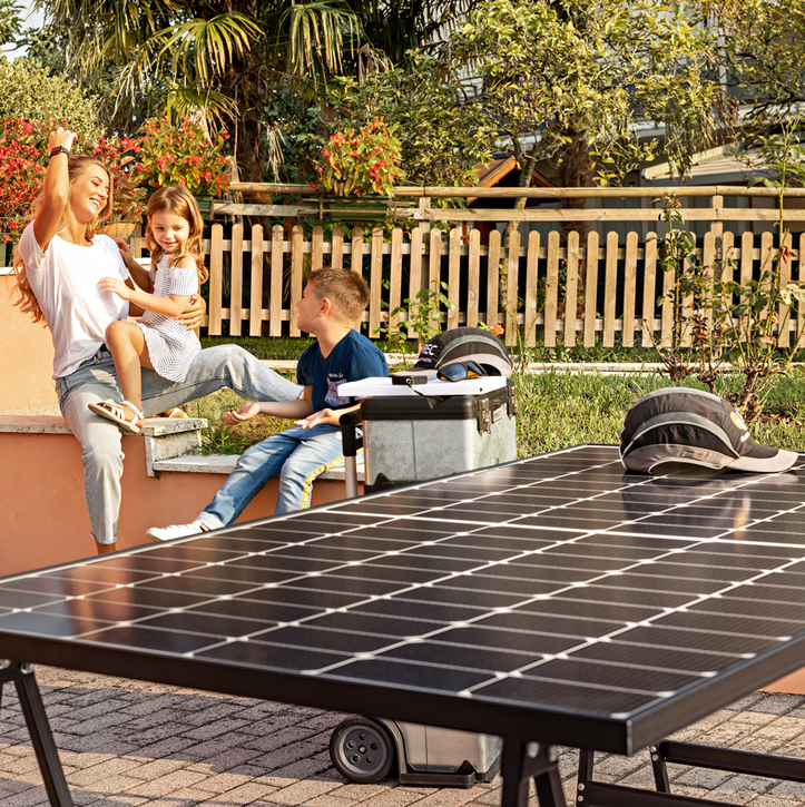 A smiling mother with her daughter and son and a single high-efficiency REC Alpha solar panel, happy with the reliability that comes with REC